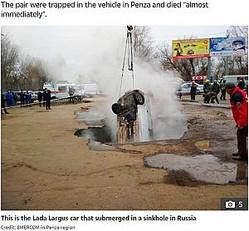 シンクホールから引き上げられる車(画像は『The Sun 2019年11月19日付「HORROR DEATH Two men boiled alive after Lada falls into car park sinkhole and fills with scalding 75C water as pipe bursts」(Credit: EMERCOM in Penza region)』のスクリーンショット)