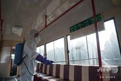 北朝鮮・平壌で路面電車の車内を消毒する作業員(2020年2月26日撮影)。(c)KIM Won Jin / AFP