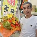 元学生から贈られた花の前に立つ井上店主。花には「学生時代お世話になりました」と書かれている(京都市上京区・餃子の王将出町店)