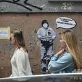 イタリア・ローマの中華街で、ストリートアーティストのライカさんが描いた壁画の前を歩く2人の女性。壁画には新型コロナウイルス流行について「無知という疫病が流行している。自分自身を守ろう!」というせりふが書かれている(2020年2月4日撮影)。(c)Filippo MONTEFORTE / AFP