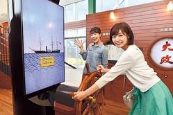 蒸気船の模型に搭乗して乗組員気分で舵を回す。本館には楽しい体験型の展示が豊富にそろう/高知県立坂本龍馬記念館