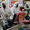 中国・武漢の薬局で、防護服とマスクを身に着けて接客する店員(2020年1月25日撮影)。(c)Hector RETAMAL / AFP