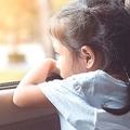 かわいい女の子が車の窓から外を見ている