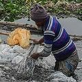 バングラデシュ首都ダッカを流れるブリガンガ川で、工業化学物質が入っていた袋を洗う男性(2020年1月9日撮影、資料写真)。(c)MUNIR UZ ZAMAN / AFP