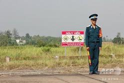 ベトナム南部ホーチミン市郊外のビエンホア空軍基地で、危険警告標識のそばに立つベトナム兵(2018年10月17日撮影、資料写真)。(c)Thomas WATKINS / AFP