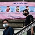 タイ・バンコクの列車の駅で、新型ウイルスに関するポスターの前を通るマスクを着けた乗客(2020年2月1日撮影)。(c)Romeo GACAD / AFP