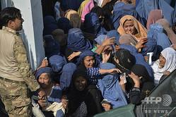 アフガニスタン・ジャララバードの女性11人が死亡した競技場のメインゲート外に集まる女性たち(2020年10月21日撮影)。(c)NOORULLAH SHIRZADA / AFP