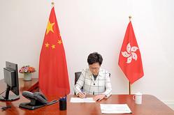 香港国家安全維持法を公布するため署名する林鄭月娥行政長官=2020年6月30日、香港、香港政府提供