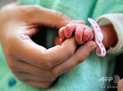 母親の指を握る新生児(2013年9月17日撮影、資料写真)。(c)PHILIPPE HUGUEN / AFP