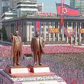 北朝鮮・平壌の金日成広場で開かれた建国70周年の祝賀行事で、故金日成国家主席と息子の故金正日総書記の像の前で旗を掲げる人々(2018年9月9日撮影、資料写真)。(c)AFP=時事/AFPBB News