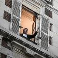 自宅の窓から「オー・ソレ・ミオ」を披露するテノール歌手。仏パリにて(2020年3月26日撮影)。(c)PHILIPPE LOPEZ / AFP