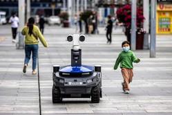 武漢市内の道を行く検温&消毒ロボット 写真/AFP・EPA=時事