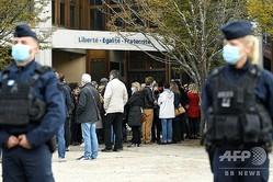 仏パリ近郊コンフランサントノリーヌで、警官が配備される中、教師殺害事件を受けて花が手向けられている中学校の入り口に向かう人々(2020年10月17日撮影)。(c)Bertrand GUAY / AFP