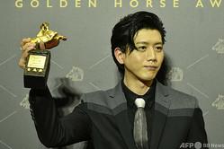 台湾・台北で開かれた映画賞「金馬奨」授賞式で、最優秀主演男優賞を受賞しトロフィーを掲げる台湾の俳優モー・ズーイー(莫子儀、2020年11月21日撮影)。(c)SAM YEH / AFP