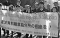 (写真)「違法有料職業紹介所の根絶を!」と横断幕を掲げ、裁判所に向かうタンさん(中央)ら=16日、東京地裁前