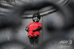 「世界肺炎デー」の服を着てマスクをしたベルギー・ブリュッセルの「小便小僧(マヌカンピス)」(2019年11月12日撮影)。(c)JOHN THYS / AFP