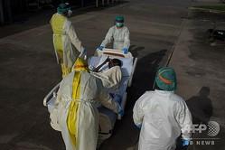 米テキサス州ヒューストンの医療機関で、新型コロナウイルス患者を運ぶ医療関係者(2020年7月2日撮影、資料写真)。(c)Mark Felix / AFP