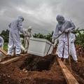 インドネシア・ボゴールで、新型コロナウイルスに感染し亡くなった人の遺体を納めたひつぎを特別墓地に埋葬する人々(2021年1月26日撮影)。(c)ADITYA AJI / AFP