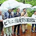 (写真)雨のなか、高知地裁に訴状提出行動をする原告や支援者=9日、高知市内