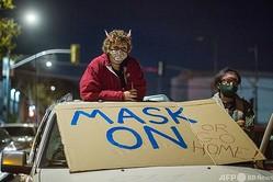 米カリフォルニア州ロサンゼルスで、新型コロナウイルスの感染が拡大するなかイベント開催を計画しているミュージシャンに抗議する人たち(2020年12月30日撮影)。(c)Patrick T. Fallon / AFP