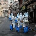 中国・上海の新型コロナウイルス感染者が確認された地区で、消毒剤の散布に向かう保健当局者ら(2021年1月27日撮影)。(c)STR / AFP