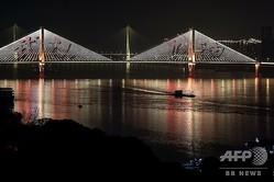 中国・湖北省武漢の橋に映し出された「武漢加油(武漢頑張れ、の意)」のメッセージ(2020年1月27日撮影)。(c)Hector RETAMAL / AFP