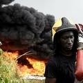 ナイジェリア・ラゴスで、宗教儀式に端を発した火災により、炎上した石油パイプラインで消火活動にあたる消防士ら(2019年12月5日撮影)。(c)PIUS UTOMI EKPEI / AFP