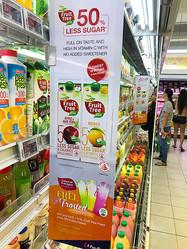 国内のスーパーでは、砂糖量をカットしたことをアピールする飲料の広告が目立った=シンガポール、守真弓撮影
