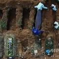 ブラジル・サンパウロ市郊外の墓地で、新型コロナウイルスの犠牲者とみられる遺体の埋葬の様子(2020年5月22日撮影)。(c)NELSON ALMEIDA / AFP