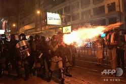 香港で、民主派のデモ参加者に向けて催涙弾を撃つ警察の機動隊員(2019年9月21日撮影)。(c)Nicolas ASFOURI / AFP