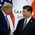 大阪市で開催された20か国・地域(G20)首脳会議(サミット)に合わせて開かれた米中首脳会談で、握手するドナルド・トランプ米大統領(左)と習近平中国国家主席(2019年6月29日撮影)。(c)Brendan Smialowski / AFP