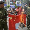 フィリピンの首都マニラの中国領事館前で、南シナ海の地図を貼った中国国旗を燃やして抗議する活動家ら(2019年6月12日撮影)。(c)TED ALJIBE / AFP