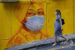 街中に描かれたグラフィティの脇を歩く妊婦。香港で(2020年3月23日撮影、資料写真)。(c)ANTHONY WALLACE / AFP)