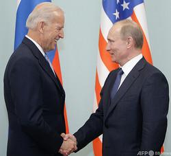 ロシア・モスクワで握手を交わす、ウラジーミル・プーチン氏(右)とジョー・バイデン氏(2011年3月11日撮影、資料写真)。(c)ALEXEY DRUZHININ / POOL / AFP