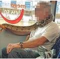 ヘビをマスク代わりに巻いた男性(画像は『Metro 2020年9月15日付「Man uses snake as a face mask on bus through Manchester」(Picture: MEN Media)』のスクリーンショット)