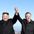 白頭山の頂上で握った手を掲げて記念撮影する文大統領(右)と金委員長(写真共同取材団)=20日、白頭山(聯合ニュース)