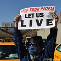 米ニューヨークで、道路を封鎖して債務免除を訴える抗議活動を行うイエローキャブの運転手ら(2021年2月10日撮影)。(c)Angela Weiss / AFP