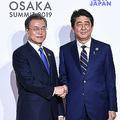 大阪で開催された20か国・地域(G20)首脳会議(サミット)で、韓国の文在寅大統領と握手する安倍晋三首相(2019年6月28日撮影)。(c)AFP=時事/AFPBB News