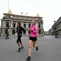 仏全土で厳格なロックダウン(都市封鎖)が実施される中、パリのオペラ座前をジョギングする人たち(2020年3月21日撮影)。(c)FRANCK FIFE / AFP