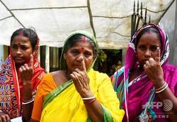 インドのコルカタの南約110キロに位置するゴラマラ島で、総選挙の投票後にインクが塗られた指を見せる有権者ら(2019年5月19日撮影)。(c)DIBYANGSHU SARKAR / AFP