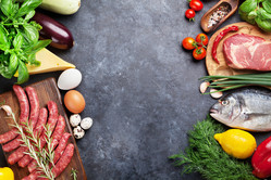 Vegetables, fish, meat and ingredients for cooking. Tomatoes, pepper, corn, beef, eggs. Top view with copy space on stone table