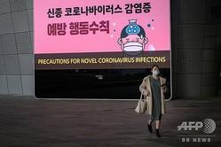 韓国・ソウルで、新型コロナウイルス予防について表示されたスクリーンの前を歩くマスク姿の女性(2020年2月11日撮影)。(c)Ed JONES / AFP
