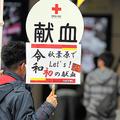 「令和初の献血」を呼びかけるボードを持つ男性=2019年5月1日午後1時41分、東京・秋葉原、長島一浩撮影