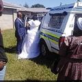 エスコートされてパトカーに乗る新婦(画像は『TimesLIVE 2020年4月5日付「WATCH | KZN newlyweds arrested for breaching Covid-19 regulations」』のスクリーンショット)