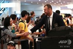 ラグビーW杯日本大会に向けて来日し、羽田空港でファンと握手するオーストラリア代表のマイケル・チェイカHC(右、2019年9月9日撮影)。(c)Behrouz MEHRI / AFP