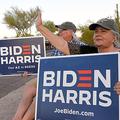 自宅前の道路沿いで、民主党のバイデン前副大統領を支持するプラカードを持ち、車に向けて手を振るリンダ・ロウルズさんと夫のトムさん=2020年9月30日午後5時44分、アリゾナ州ケアフリー、鵜飼啓撮影