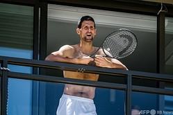 全豪オープンテニスを控え、アデレードにある隔離先のホテルのバルコニーからファンとやり取りするノバク・ジョコビッチ(2021年1月20日撮影)。(c)Morgan SETTE / AFP