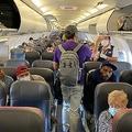 米ニューヨーク発ノースカロライナ州シャーロット行きのアメリカン航空の機内。乗客の大半がマスクを着用している(2020年5月3日撮影)。(c)Eleonore SENS / AFP