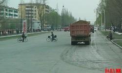 元山葛麻海岸観光地区の建設でダンプカーが急増した元山市内の通りを自転車が横切っている。(画像:デイリーNK内部情報筋)