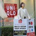 ソウル市内のユニクロ店舗前で、学生団体のメンバーが日本による植民地時代の戦犯企業などを批判する1人デモを行っている(資料写真)=(聯合ニュース)